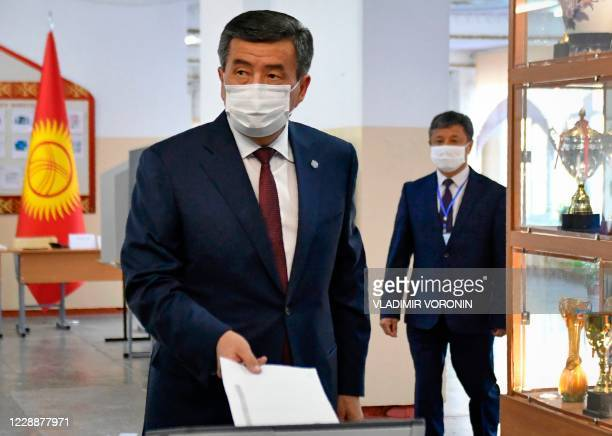 Kyrgyz President Sooronbay Jeenbekov wearing a face mask casts his ballot at a polling station during parliamentary election in Bishkek on October 4...