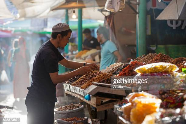 Kyrgyz seller arranging dried fruit and spices at food market stall in the city Osh along the Silk Road in Kyrgyzstan.