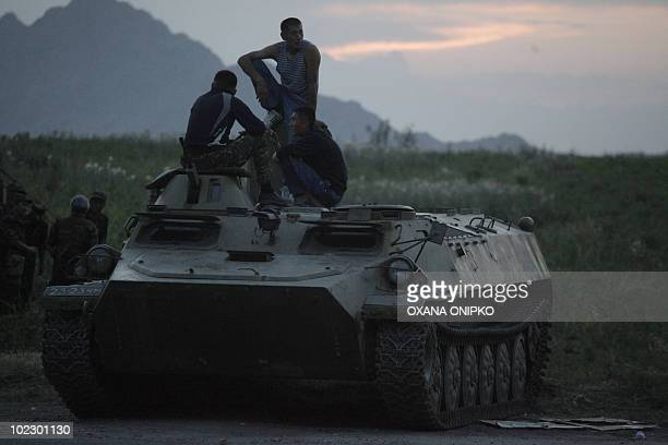 Kyrgyz soldiers in plain clothes sit on top of an armoured vehicle in Osh on June 20, 2010. Kyrgyzstan's military on Sunday cleared makeshift...