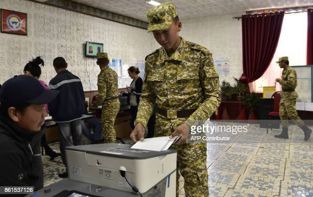 Kyrgyz soldiers vote at a polling station during the presidential election in the village of KyzylBirlik some 30 km from Bishkek on October 15 2017...