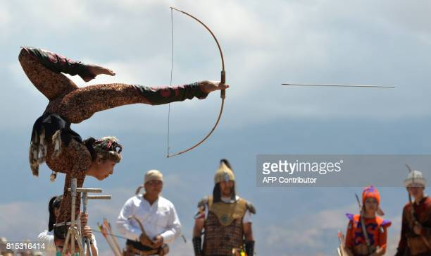 A Kyrgyz woman balances on her hands as she shoots a bow and arrow with her feet during the 'Ethno Fest' festival in the village of Ton near IssykKul...
