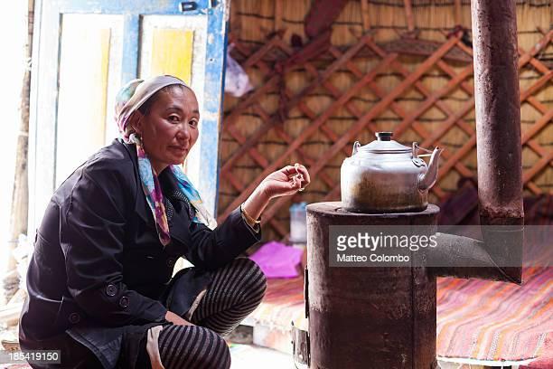 Kyrgyz woman preparing tea inside a yurt