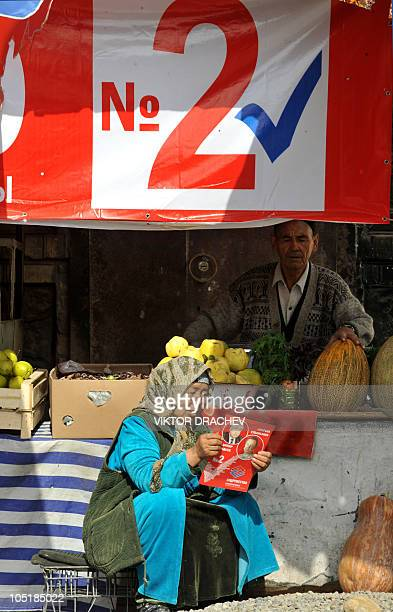 Kyrgyz woman reads a pre-election leaflet at a street market in Osh on October 8, 2010. Kyrgyzstan's parties Friday made a final push for votes in...