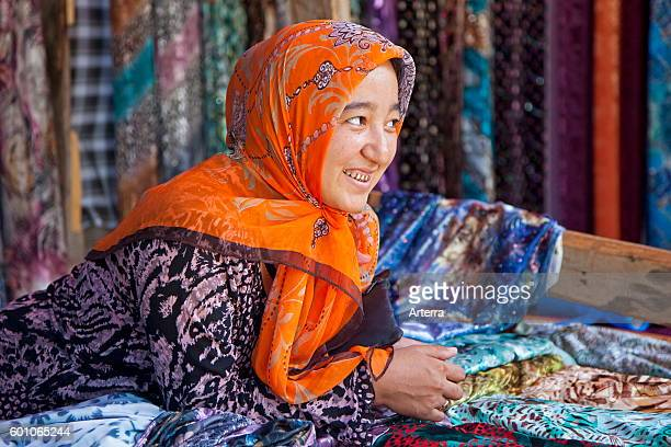 Kyrgyz woman with golden teeth selling colourful fabrics at market in Osh Kyrgyzstan