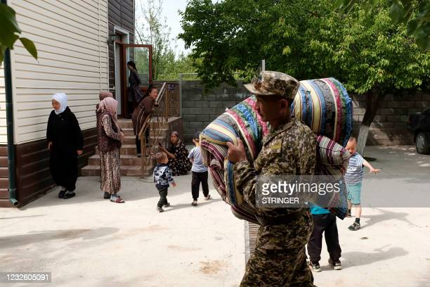 Kyrgyzstan's emergencies ministry serviceman carries mattresses for citizens, who were evacuated from districts bordering Tajikistan following the...