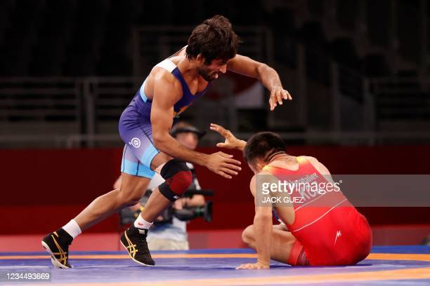 Kyrgyzstan's Ernazar Akmataliev wrestles India's Bajrang Bajrang in their men's freestyle 65kg wrestling early round match during the Tokyo 2020...