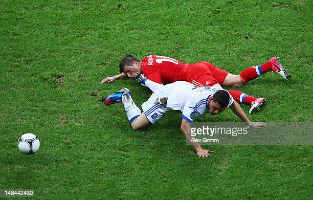 Kyriakos of Greece and Andrey Arshavin of Russia fall to the pitch as they battle for the ball during the UEFA EURO 2012 group A match between Greece...