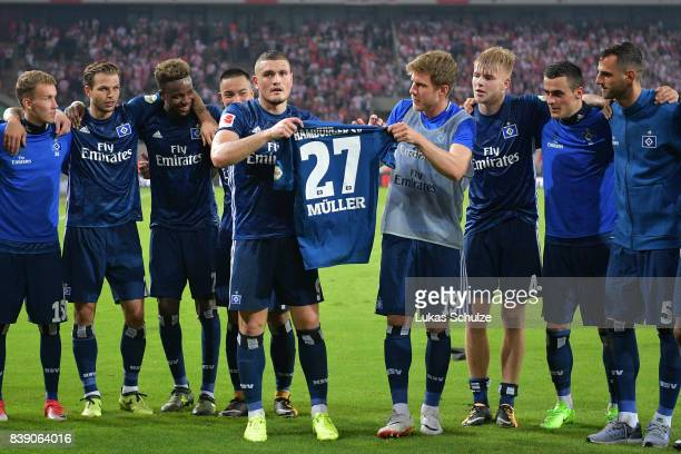 Kyriakos Papadopoulos of Hamburg and Andre Hahn of Hamburg hold the shirt of Nicolai Mueller of Hamburg who is out for month due to injury after the...
