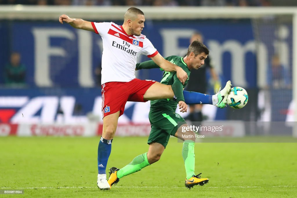 Kyriakos Papadopoulos of Hamburg (l) fights for the ball with Fin Bartels of Bremen during the Bundesliga match between Hamburger SV and SV Werder Bremen at Volksparkstadion on September 30, 2017 in Hamburg, Germany.