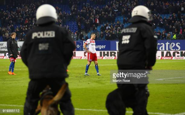 Kyriakos Papadopoulos of Hamburg stands as police forces enter the pitch with dogs in front of the Hamburg stand after the Bundesliga match between...