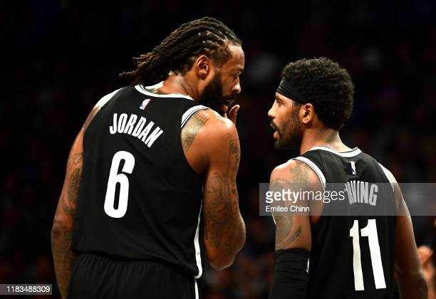 Kyrie Irving and DeAndre Jordan of the Brooklyn Nets talk during the second half of their game against the New York Knicks at Barclays Center on...