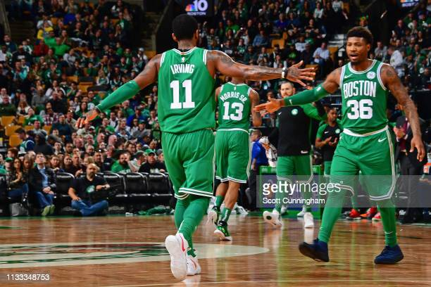 Kyrie Irving and Marcus Smart of the Boston Celtics high five against the Atlanta Hawks on March 16 2019 at the TD Garden in Boston Massachusetts...