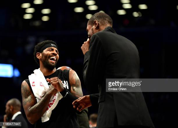 Kyrie Irving laughs with Kevin Durant of the Brooklyn Nets during a time out in the first half of their game against the New York Knicks at Barclays...