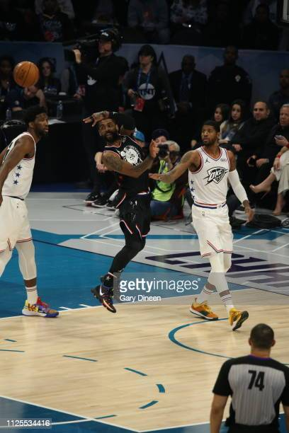 Kyrie Irving of Team LeBron passes against Joel Embiid and Paul George of Team Giannis during the 2019 NBA AllStar Game on February 17 2019 at the...
