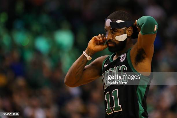 Kyrie Irving of the Boston Celtics adjusts his face mask during the second half against the Phoenix Suns at TD Garden on December 2 2017 in Boston...