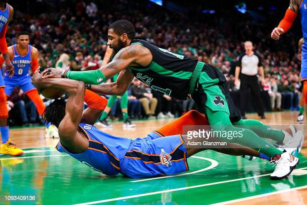 Kyrie Irving of the Boston Celtics and Jerami Grant of the Oklahoma City Thunder fight for a loose ball during a game at TD Garden on February 3 2019...