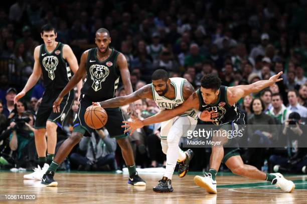 Kyrie Irving of the Boston Celtics and Malcolm Brogdon of the Milwaukee Bucks battle for a loose ball during the second half at TD Garden on November...