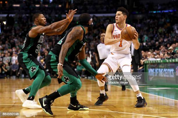 Kyrie Irving of the Boston Celtics and Marcus Smart defend Devin Booker of the Phoenix Suns during the second half at TD Garden on December 2 2017 in...