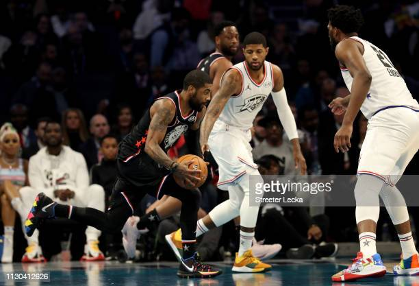 Kyrie Irving of the Boston Celtics and Team LeBron drives to the basket against Joel Embiid of the Philadelphia 76ers and teammate Paul George of the...