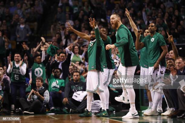 Kyrie Irving of the Boston Celtics Aron Baynes and Al Horford celebrate on the sideline during the second half against the Dallas Mavericks at TD...