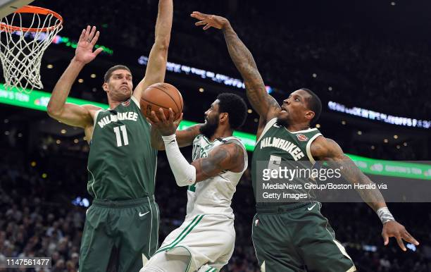 Kyrie Irving of the Boston Celtics attempts a shot past Milwaukee Bucks defenders Brook Lopez left and Eric Bledsoe during the third quarter of Game...