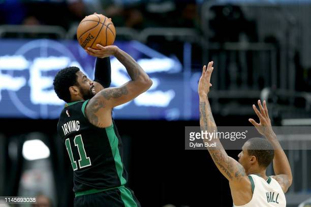 Kyrie Irving of the Boston Celtics attempts a shot while being guarded by George Hill of the Milwaukee Bucks in the fourth quarter during Game One of...