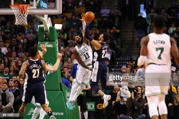 Kyrie Irving of the Boston Celtics defends a shot by Jamal Murray of the Denver Nuggets during the second half at TD Garden on December 13 2017 in...