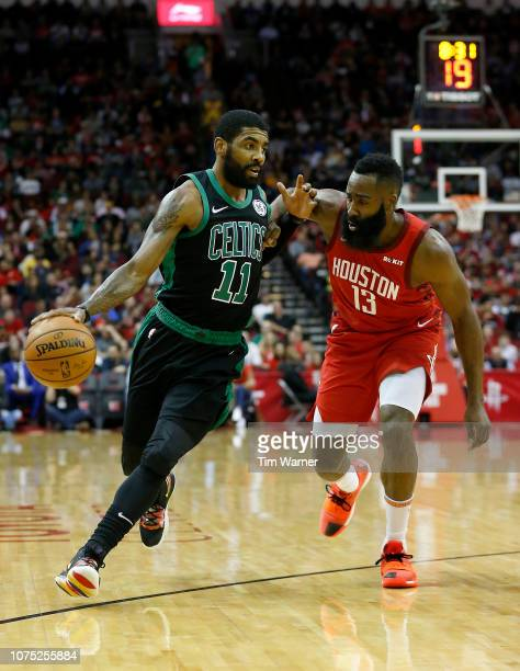 Kyrie Irving of the Boston Celtics dribbles the ball defended by James Harden of the Houston Rockets in the first half at Toyota Center on December...