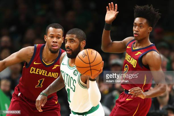 Kyrie Irving of the Boston Celtics dribbles the ball while guarded by Rodney Hood and Collin Sexton of the Cleveland Cavaliers during a game at TD...