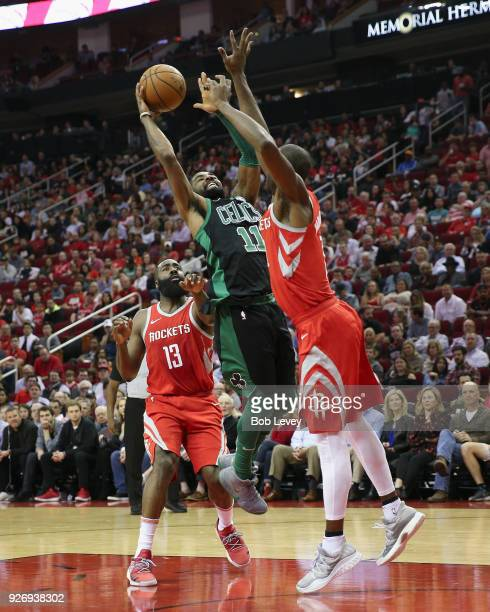 Kyrie Irving of the Boston Celtics drives between James Harden of the Houston Rockets and Chris Paul at Toyota Center on March 3 2018 in Houston...