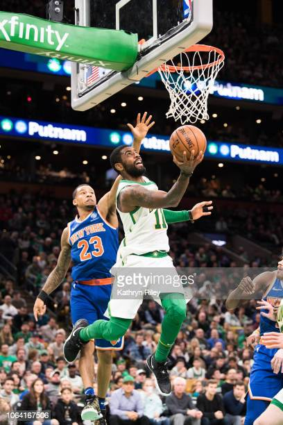 Kyrie Irving of the Boston Celtics drives past Trey Burke of the New York Knicks during a game at TD Garden on November 21 2018 in Boston...