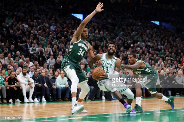Kyrie Irving of the Boston Celtics drives to the basket between Giannis Antetokounmpo and Eric Bledsoe of the Milwaukee Bucks during the first...