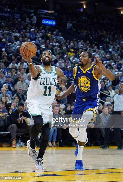 Kyrie Irving of the Boston Celtics drives to the basket on Kevin Durant of the Golden State Warriors during an NBA basketball game at ORACLE Arena on...