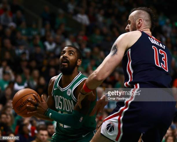 Kyrie Irving of the Boston Celtics drives to the basket on Marcin Gortat of the Washington Wizards during the game against the Washington Wizards at...