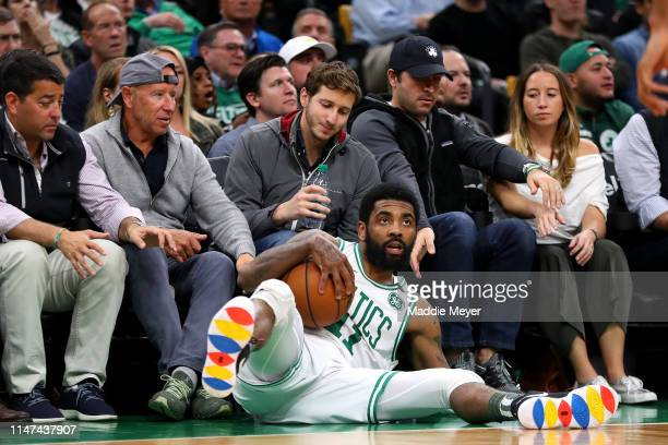 Kyrie Irving of the Boston Celtics falls into fans during the second half of Game 4 of the Eastern Conference Semifinals against the Milwaukee Bucks...