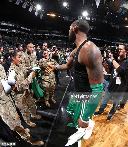 Kyrie Irving of the Boston Celtics gives his jersey and sneakers away to military veterns after the game against the Brooklyn Nets on November 14...