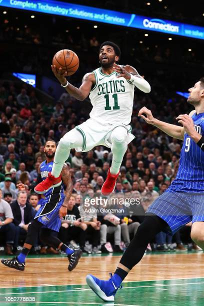 Kyrie Irving of the Boston Celtics goes up for a layup while guarded by Nikola Vucevic of the Orlando Magic during a game at TD Garden on October 22...
