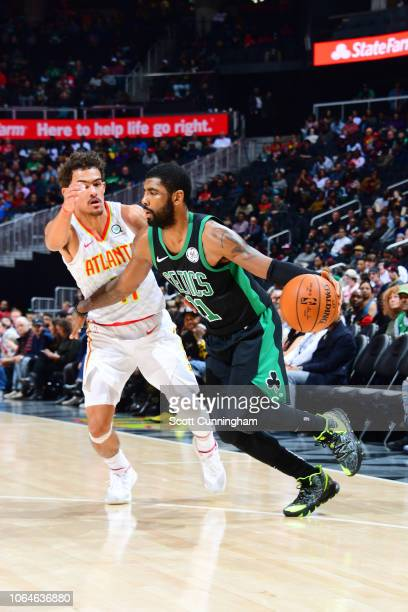 Kyrie Irving of the Boston Celtics handles the ball against Trae Young of the Atlanta Hawks on November 23 2018 at State Farm Arena in Atlanta...
