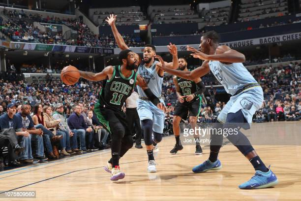 Kyrie Irving of the Boston Celtics handles the ball between Garrett Temple and Jaren Jackson Jr #13 of the Memphis Grizzlies on December 29 2018 at...