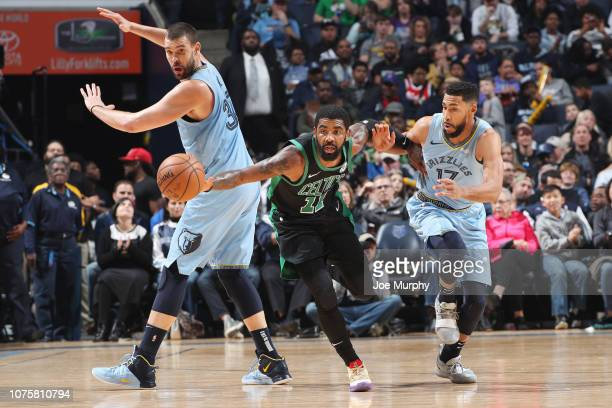 Kyrie Irving of the Boston Celtics handles the ball between Marc Gasol and Garrett Temple of the Memphis Grizzlies during the game on December 29...