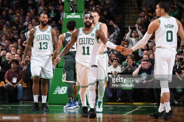 Kyrie Irving of the Boston Celtics high fives Jayson Tatum during the game against the Milwaukee Buckson December 4 2017 at the TD Garden in Boston...