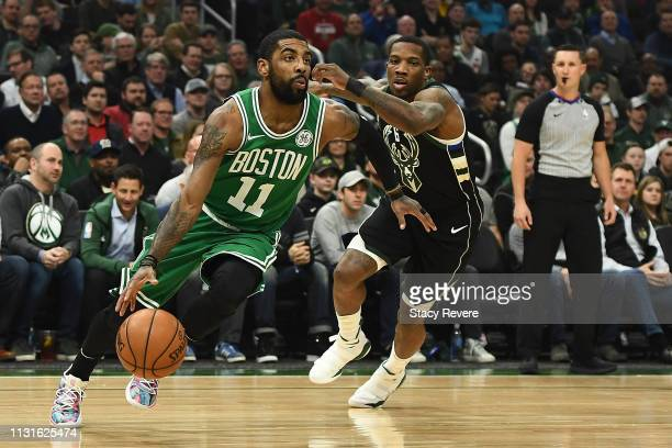 Kyrie Irving of the Boston Celtics is defended by Eric Bledsoe of the Milwaukee Bucks during a game at Fiserv Forum on February 21 2019 in Milwaukee...