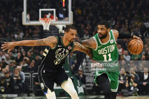 Kyrie Irving of the Boston Celtics is defended by George Hill of the Milwaukee Bucks during a game at Fiserv Forum on February 21 2019 in Milwaukee...