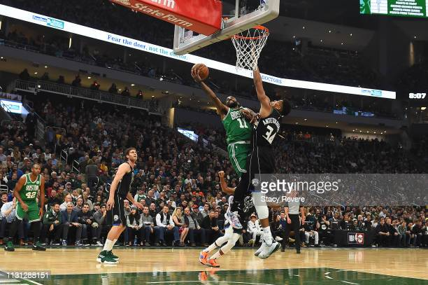 Kyrie Irving of the Boston Celtics is defended by Giannis Antetokounmpo of the Milwaukee Bucks during the first half of a game at Fiserv Forum on...