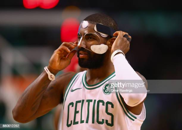Kyrie Irving of the Boston Celtics puts on his mask during the second quarter of the game against the Detroit Pistons at TD Garden on November 27...