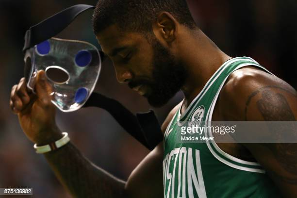 Kyrie Irving of the Boston Celtics removes his face mask worn for a facial fracture during the third quarter against the Golden State Warriors at TD...
