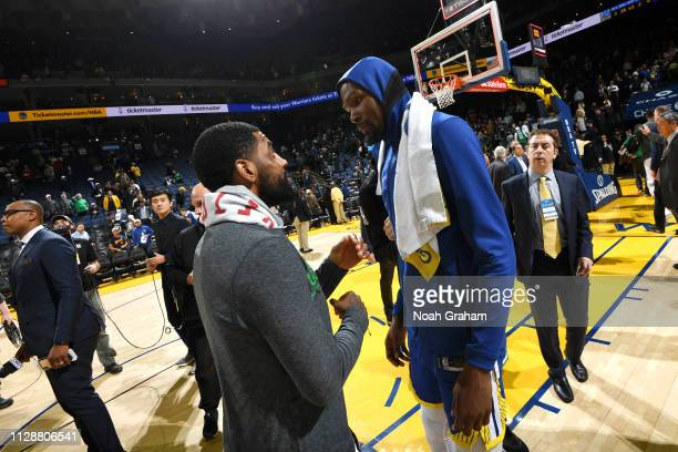 Kyrie Irving of the Boston Celtics speaks with Kevin Durant of the Golden State Warriors after the game on March 5 2019 at ORACLE Arena in Oakland...