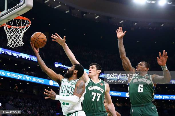 Kyrie Irving of the Boston Celtics takes a shot against Ersan Ilyasova and Eric Bledsoe of the Milwaukee Bucks during the first quarter of Game 4 of...