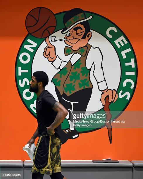Kyrie Irving of the Boston Celtics walks past a Celtics logo after a team workout at the Auerbach Center in Boston Massachusetts on April 24 2019