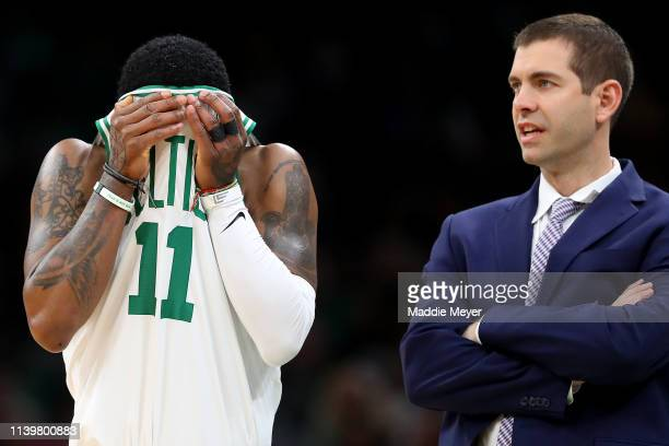 Kyrie Irving of the Boston Celtics wipes his face next to the Celtics coach Brad Stevens during the second quarter at TD Garden on April 01 2019 in...